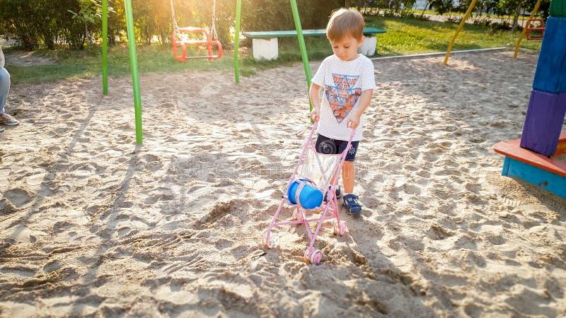3 Jahre alte Kleinkindjunge, die mit Pram für Puppen auf dem Spielplatz spielen lizenzfreie stockbilder