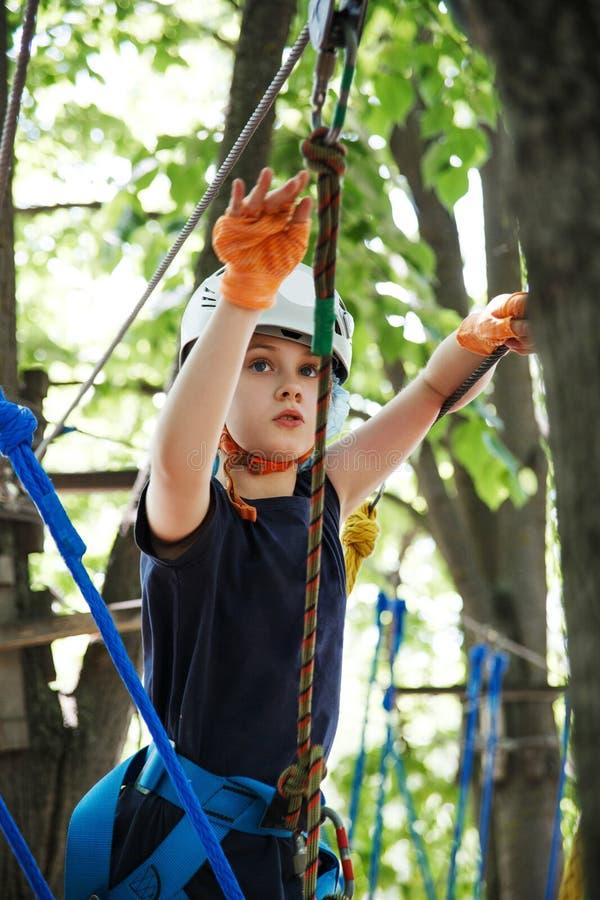 8 Jahre alte Mädchen im Walderlebnispark Kinderaufstieg auf hoher Seilspur Spielplatz im Freien mit Seilweise lizenzfreie stockfotografie