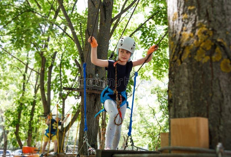 8 Jahre alte Mädchen im Walderlebnispark Kinderaufstieg auf hoher Seilspur Spielplatz im Freien mit Seilweise lizenzfreies stockfoto