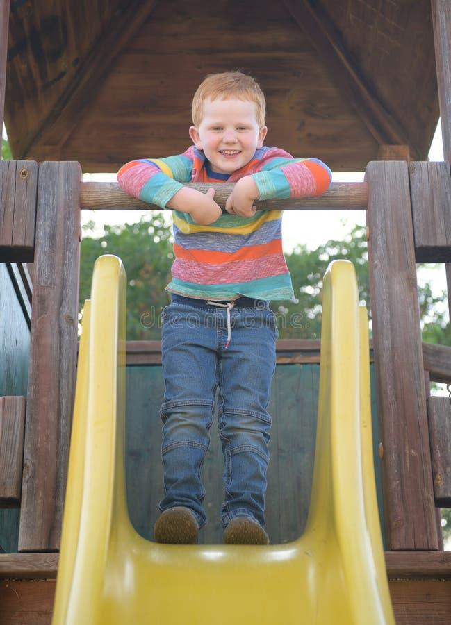 5 Jahre alte redheaded glückliche Junge, die auf einem Dia lächeln lizenzfreie stockfotos