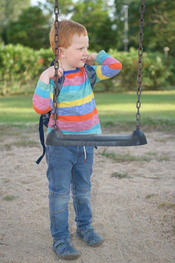 5 Jahre alte redheaded glückliche Junge, die seinen Rucksack nahe bei einem Schwingen und einem Tagtraum behandeln lizenzfreie stockbilder