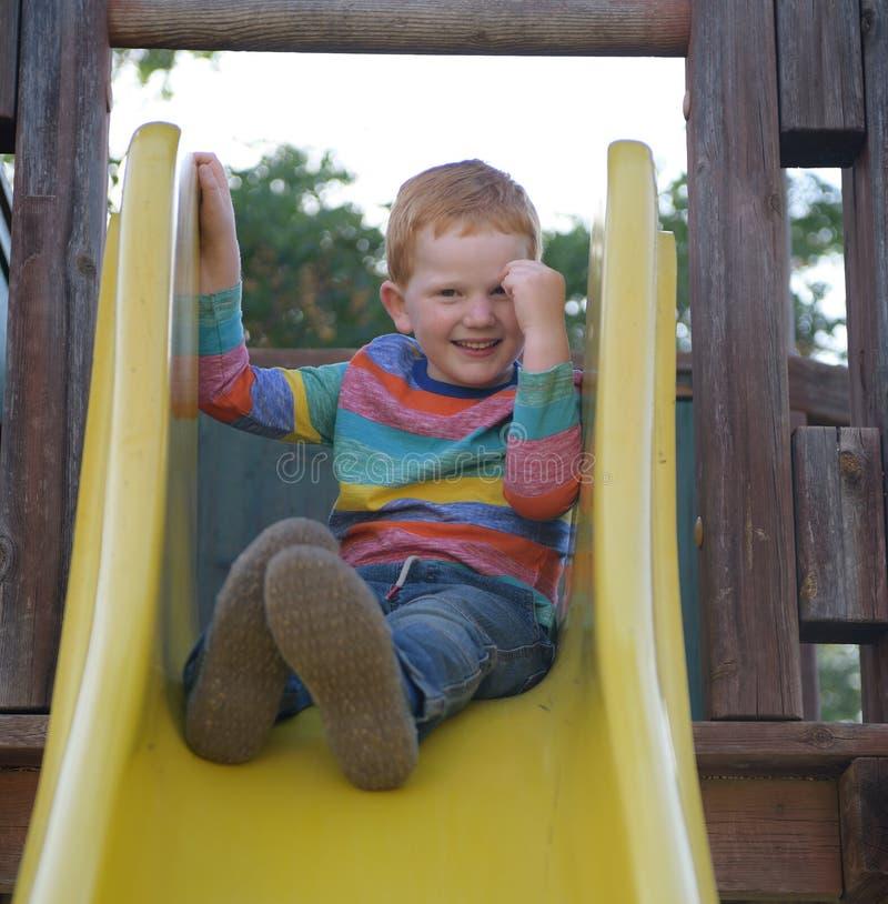 5 Jahre alte redheaded glückliche Junge sitzt auf einem Dia und einem Lächeln stockfotos