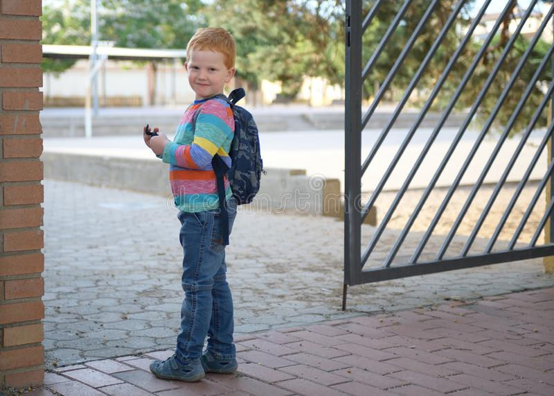 5 Jahre alte redheaded glückliche Junge vor Schule lizenzfreies stockfoto
