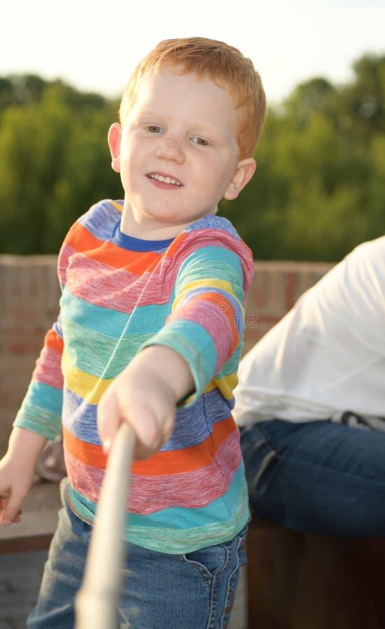 5 Jahre alte redheaded glückliche Jungenporträt Spielen mit der Kamera lizenzfreies stockbild