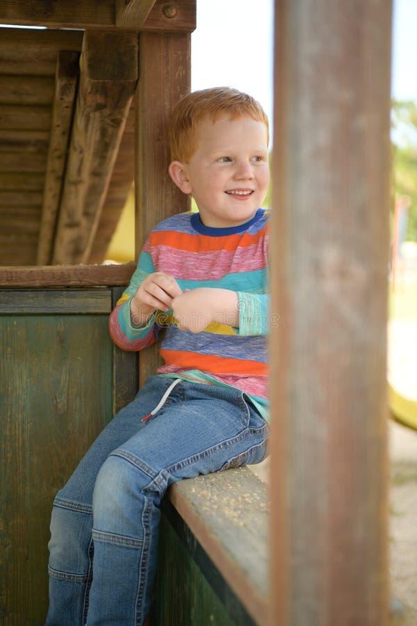 5 Jahre alte redheaded glückliche sitzende und lächelnde Junge lizenzfreie stockfotografie