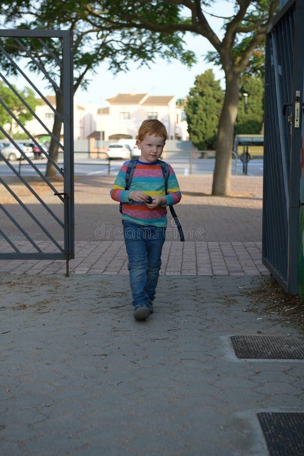 5 Jahre alte redheaded Junge, welche die Schule betreten Er ist ein wenig trauriges stockfotografie