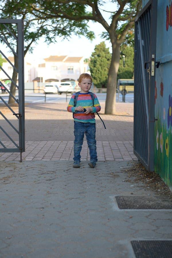 5 Jahre alte redheaded Jungenstellung vor Schule Er ist ein wenig trauriges stockfotos