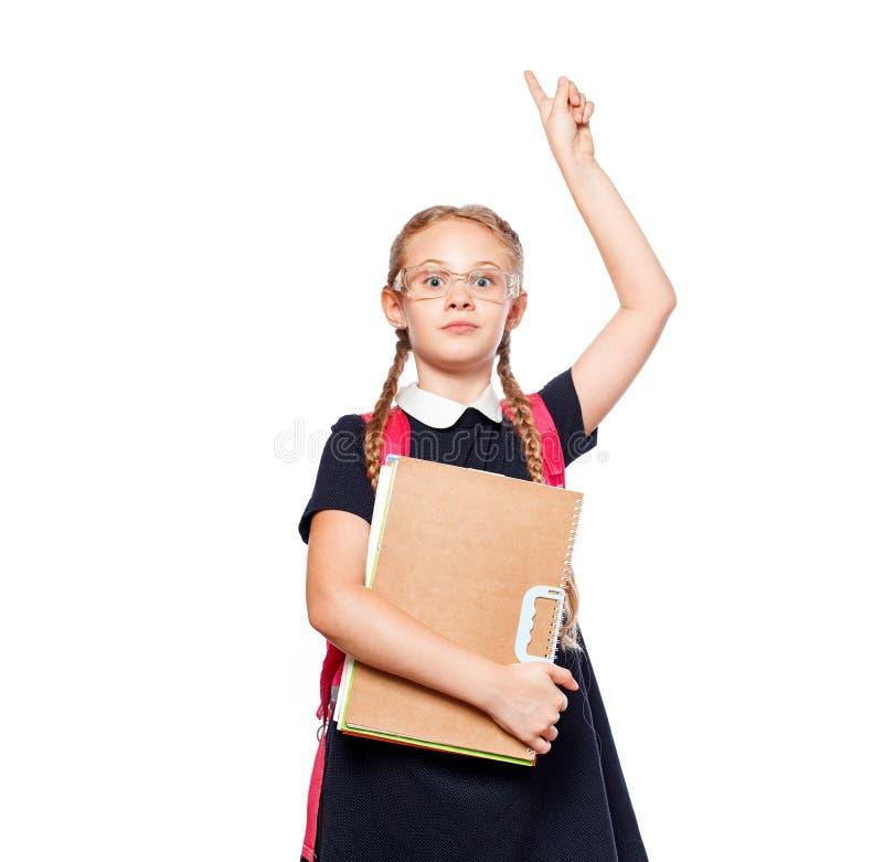 8 Jahre alte Schulmädchen mit einem Rucksack, der einheitliche Stellung lokalisiert über einem weißen Hintergrund trägt Bereiten  stockbild