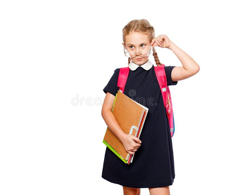 8 Jahre alte Schulmädchen mit einem Rucksack, der einheitliche Stellung lokalisiert über einem weißen Hintergrund trägt Bereiten  stockfotografie