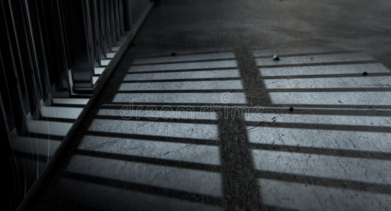 Jail Cell Bars Cast Shadows. A closeup of view of a jail cells iron bars casting shadows on the prison floor with copy space stock images