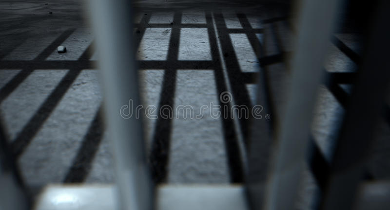 Jail Cell Bars Cast Shadows. A closeup of view of a jail cells iron bars casting shadows on the prison floor with copy space royalty free stock photos
