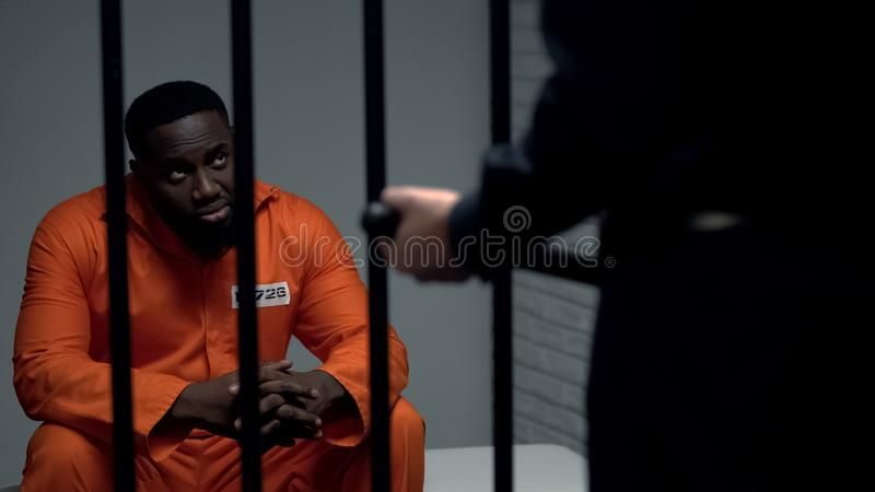 Jail guard with baton looking at afro-american prisoner in cell, harassment stock images