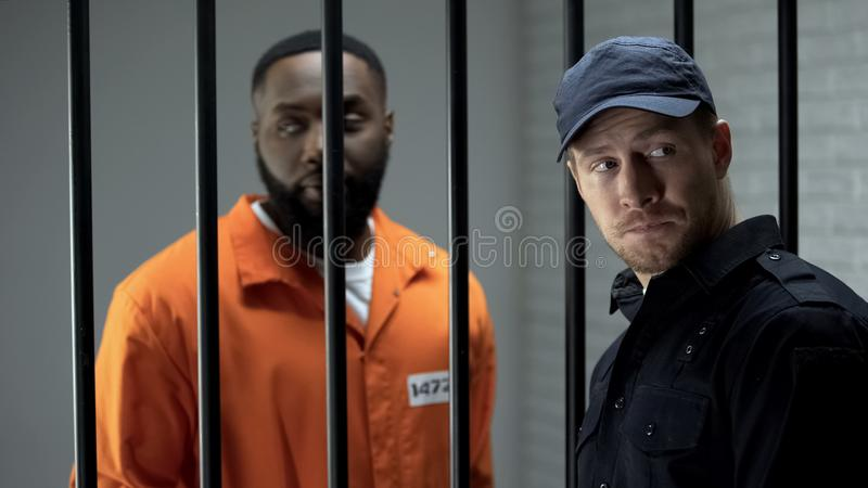 Jail guard and criminal looking back, making arrangement, corruption and bribery. Stock photo royalty free stock photo
