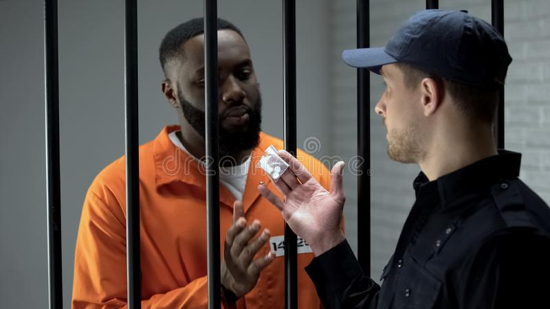 Jail guard giving african-american prisoner packet with pills, illegal activity. Stock photo stock image