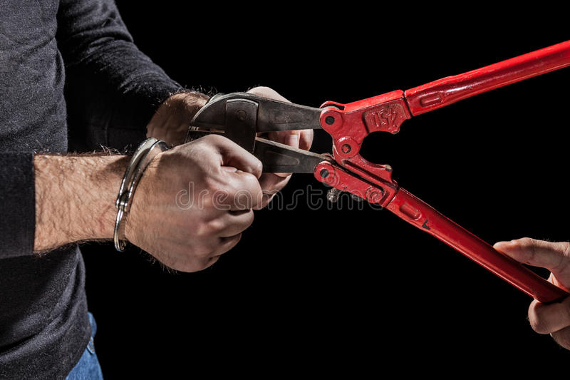 Jailbreak. Criminals that try to break handcuffs with a big pair of shears stock image