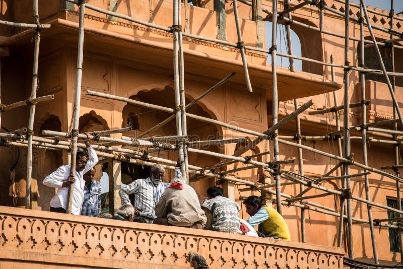 JAIPUR, ÍNDIA - 12 DE JANEIRO DE 2018: Os construtores dos homens estão descansando scaffolding Reparo de construções históricas imagem de stock