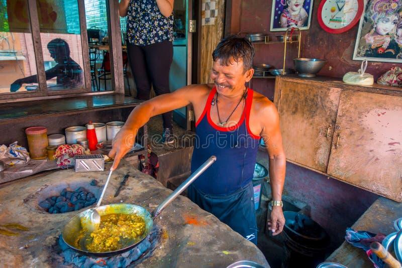 Jaipur, Índia - 20 de setembro de 2017: Homem não identificado que cozinha o alimento indiano em uma bandeja metálica sobre rocha fotos de stock royalty free