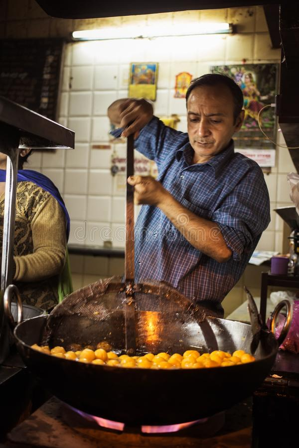 JAIPUR, ΙΝΔΙΑ - 10 ΙΑΝΟΥΑΡΊΟΥ 2018: Ένα άτομο μαγειρεύει τα παραδοσιακά ινδικά γλυκά στοκ φωτογραφία