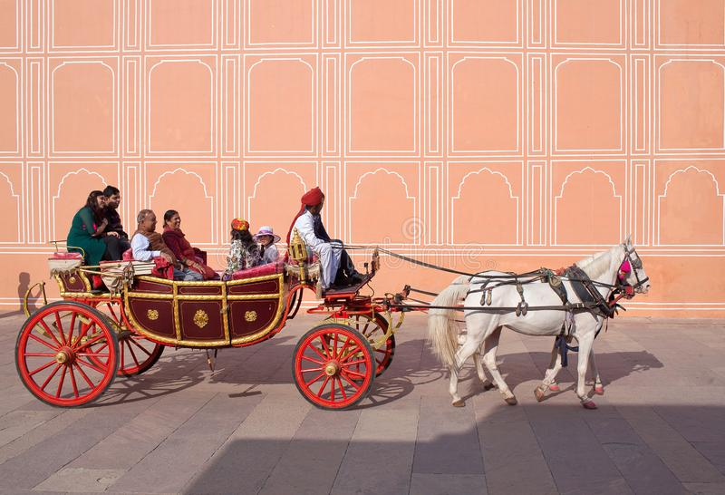 Indian tourists riding a horse cart in famous Jaipur City Palace. JAIPUR, INDIA - JANUARY 4, 2019: Happy Indian tourists riding a horse cart in famous Jaipur royalty free stock images