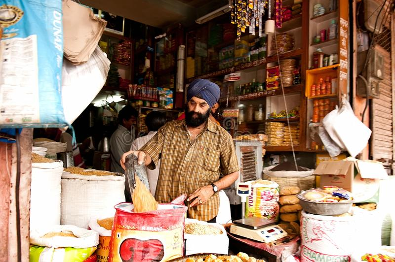 Jaipur, India - Jule 29: grocery store, man in a turban pours grain into a sack on Jule 29, 2011, Jaipur, India. stock photography