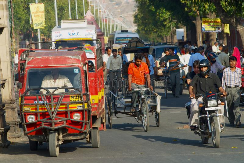 People ride by the street during morning rush hour in Jaipur, India. Jaipur, India - March 30, 2007: Unidentified people ride by the street during morning rush royalty free stock photo