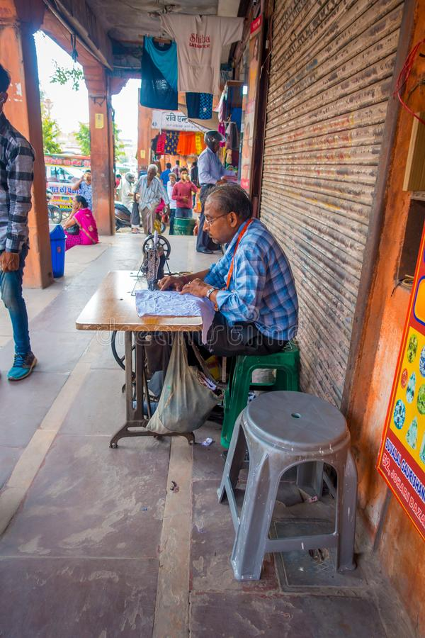Jaipur, India - September 20, 2017: A man stitching clothes with his sewing machine in Jaipur. In India royalty free stock images