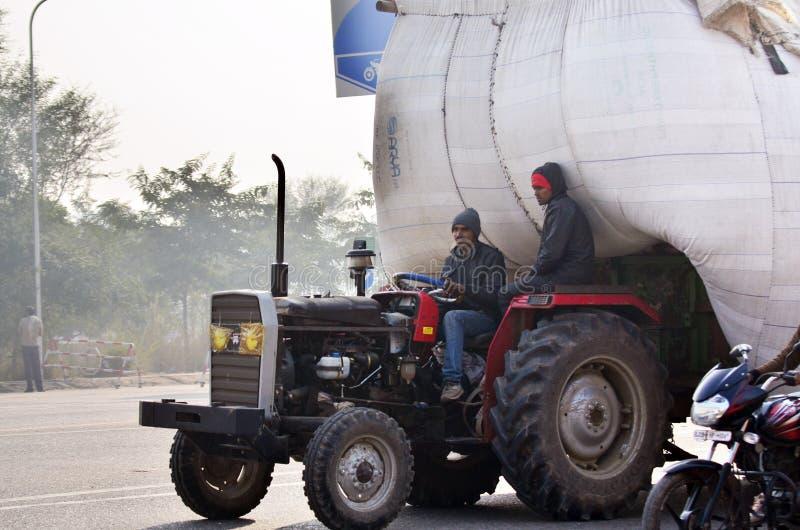 Jaipur Indien - December 30, 2014: Indisk man som kör den tungt överlastade lastbilen i Jaipur royaltyfri foto