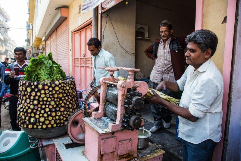 JAIPUR, LA INDIA - 10 DE ENERO DE 2018: Los hombres exprimen el jugo fresco natural de la caña de azúcar con un dispositivo mecán foto de archivo libre de regalías