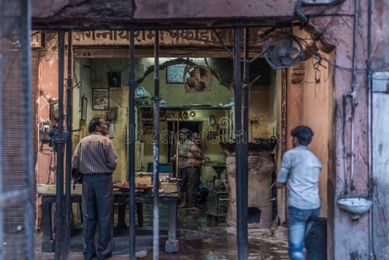 Jaipur, la India - 5 de febrero de 2017: vendedor y gente de comida en una calle sucia en Jaipur, Rajasthán, destino famoso del v foto de archivo