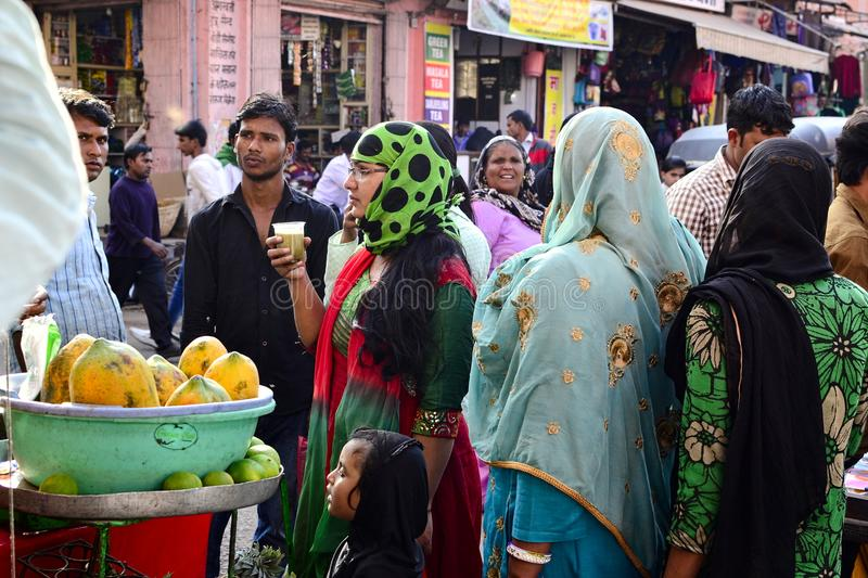 Indian woman drinks fruit juice on the street market. Jaipur, Rajasthan, India - November, 2016: Indian woman in hijab surrounded other people men and women royalty free stock photos
