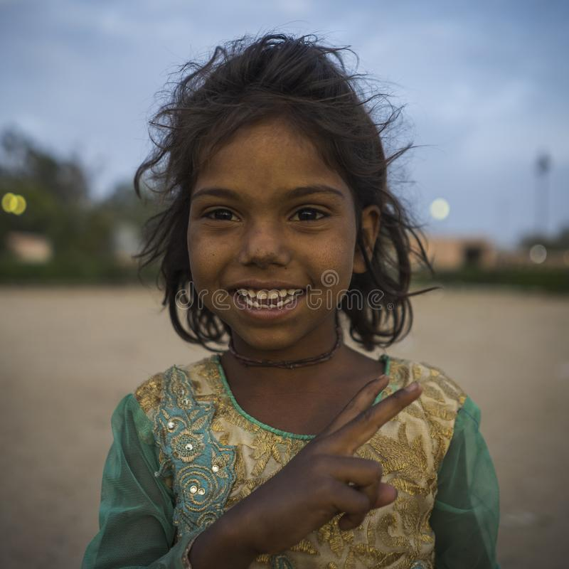 Portrait of young poor smiling girl in India. Jaipur, Rajasthan / India - 03 24 2019, Portrait of young smiling girl, Poor child in the slum area of the city royalty free stock photos