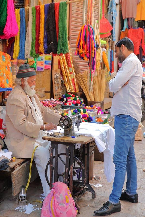 JAISALMER, RAGIASTAN, INDIA - 19 DICEMBRE 2017: Un uomo del sarto che lavora alla sua macchina per cucire fuori del suo negozio immagine stock