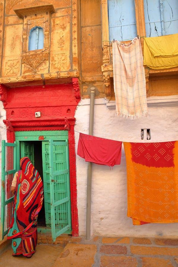 JAISALMER, RAJASTHÁN, LA INDIA - 19 DE DICIEMBRE DE 2017: La entrada colorida de un Haveli restaurado con una mujer se vistió con fotografía de archivo