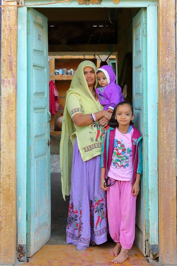 JAISALMER, RAJASTHÁN, LA INDIA - 18 DE DICIEMBRE DE 2017: Retrato de una mujer con sus dos niños en la entrada de su casa imágenes de archivo libres de regalías