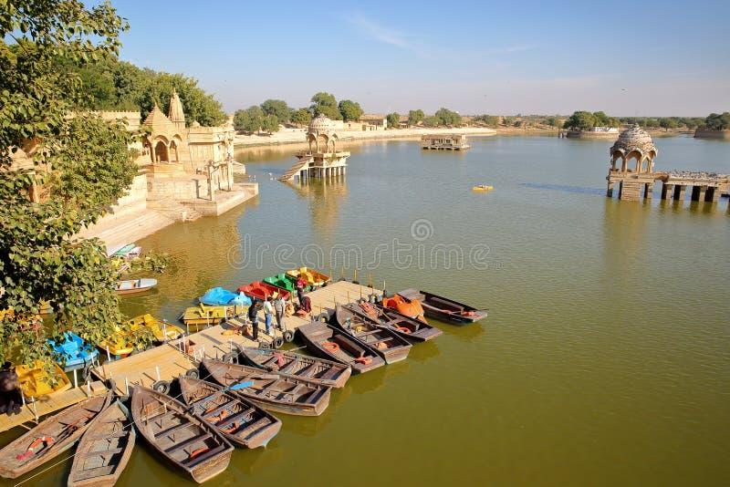 JAISALMER, RAJASTHÁN, LA INDIA - 19 DE DICIEMBRE DE 2017: Vista general del lago gadi Sagar con los barcos de batimiento en el pr fotografía de archivo