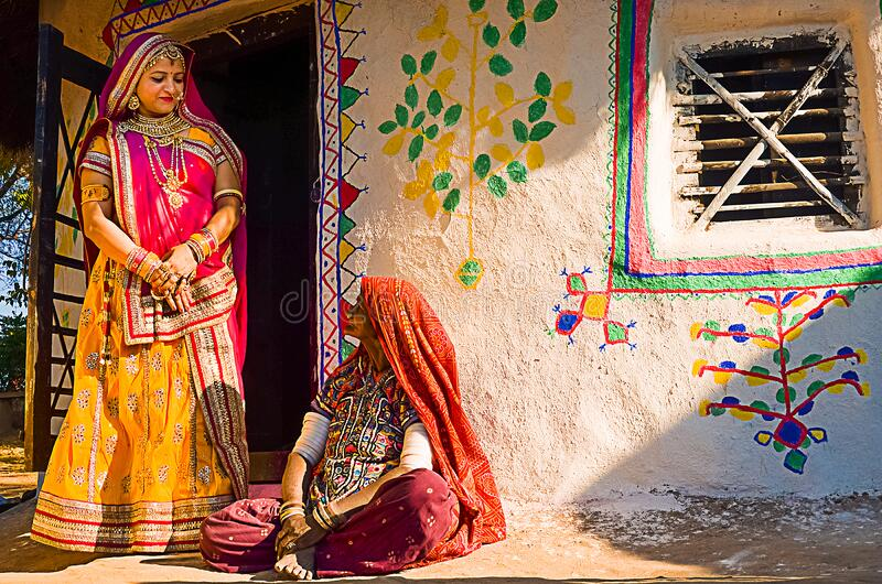Indian village women outside their house wearing ethnic traditional outfits,. Jaisalmer, rajasthan, india - april 18th, 2018: Indian village women outside their royalty free stock images