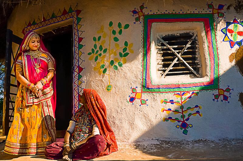 Indian village women outside their house wearing ethnic traditional outfits,. Jaisalmer, rajasthan, india - april 18th, 2018: Indian village women outside their stock images