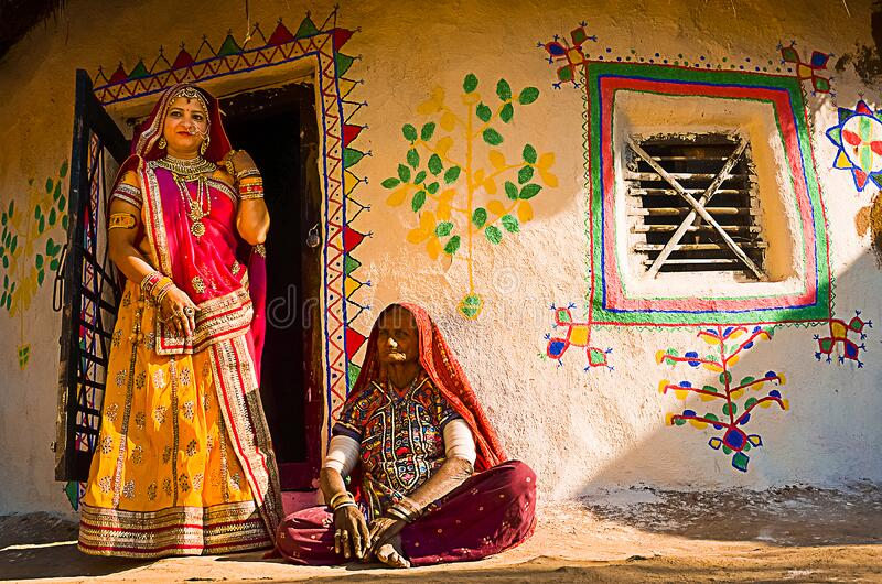 Indian village women outside their house wearing ethnic traditional outfits,. Jaisalmer, rajasthan, india - april 18th, 2018: Indian village women outside their stock photography