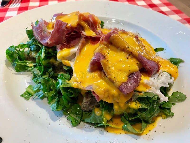 Jajeczny Benedykt z bekonem i sałatką Słuzyć przy restauracją dla śniadania obraz stock