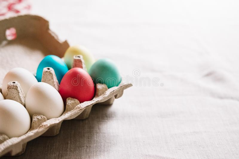 Jajeczny pudełko z kolorowymi Easter jajek stojakami na bieliźnianej kanwie zdjęcia stock