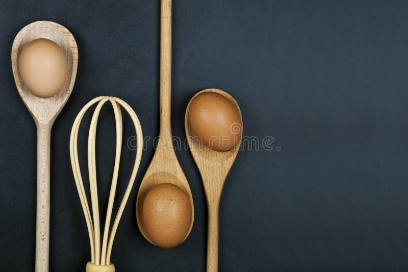 Jajka, drewniana łyżka i bokobrody, Kuchenny naczynie dla torta, ciasta lub ciastek na backboard tle, obraz royalty free