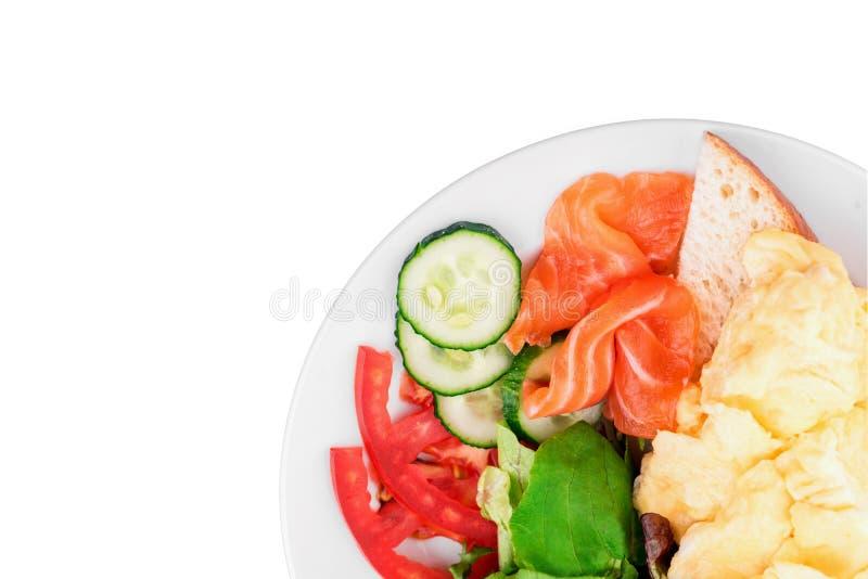 Jajka Gramolą się z łososiem, grzanka, świezi warzywa i sałata opuszcza w białym talerzu odizolowywającym na białym tle fotografia royalty free