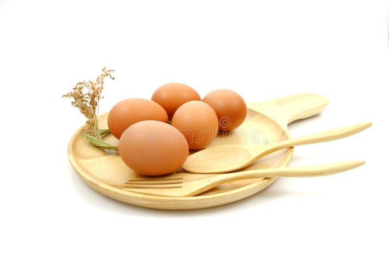 Jajko na drewnianym talerzu i wysuszona trawa kwitniemy zdjęcia stock