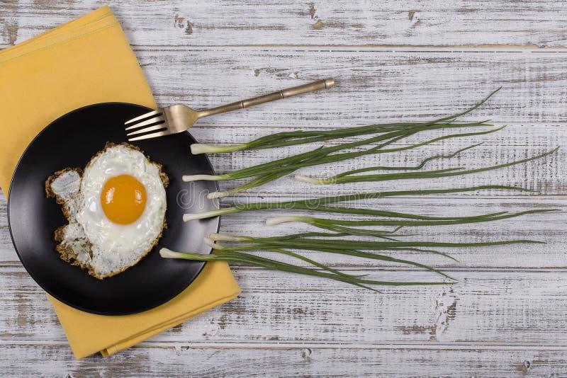 Jajko, szczypiorki i czarnego talerza spojrzenie jak spermy rywalizacja, Spermatozoons unosi się zalążek w białym drewnianym tle obrazy royalty free