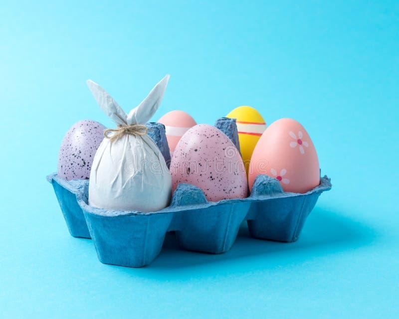 Jajko zawijający w papierze w formie królika z kolorowymi Wielkanocnymi jajkami w karton tacy Minimalny Easter pojęcie zdjęcia royalty free