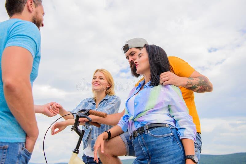 Jak bicykl zmieniał społeczeństwa Dobiera się spotkanie rozochoconych przyjaciół z bicyklem podczas spaceru Grupowi przyjaciele w zdjęcia royalty free