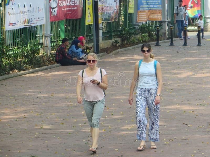 Jakarta city street. JAKARTA, INDONESIA - August 2, 2018: Two Caucasian women walking on pedestrian sidewalk on Jalan Merdeka Selatan royalty free stock photography