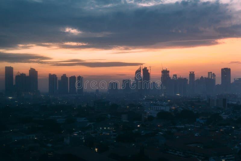 Jakarta Cityscape med hög löneförhöjning, skyskrapor och röda lokala byggnader för tegelplattahöfttak med dimma och ottahimmel på fotografering för bildbyråer