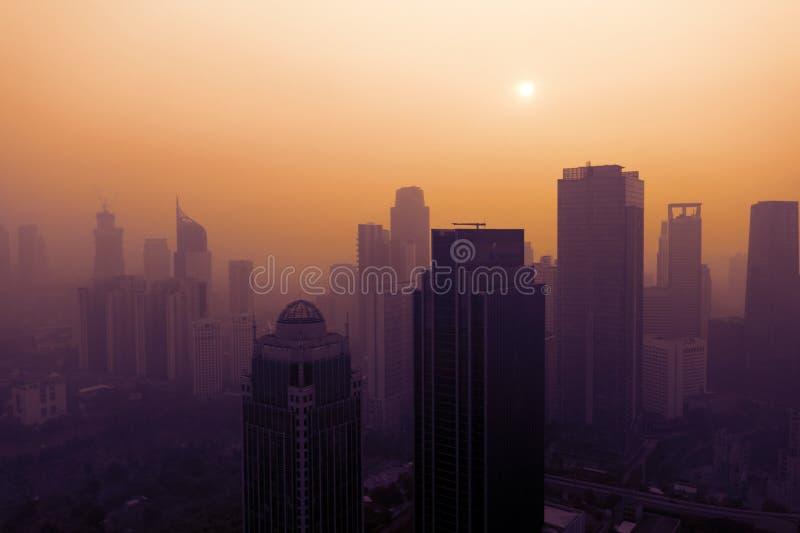 Jakarta cityscape täckte vid dammsmog på solnedgången royaltyfria foton