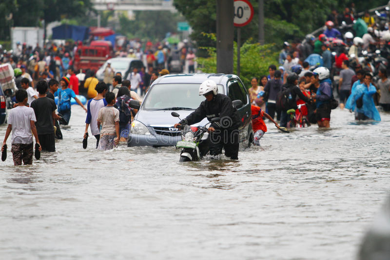 Jakarta Flood. People, motorcycles and cars crossing the flood in Jakarta